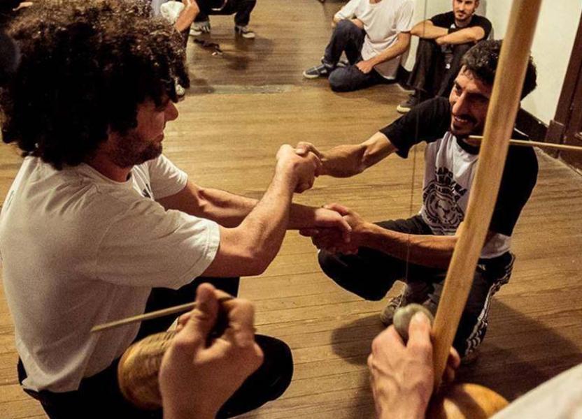 Dos jóvenes tenidos de la mano realizando Capoeira rodeado por el resto de los participantes.