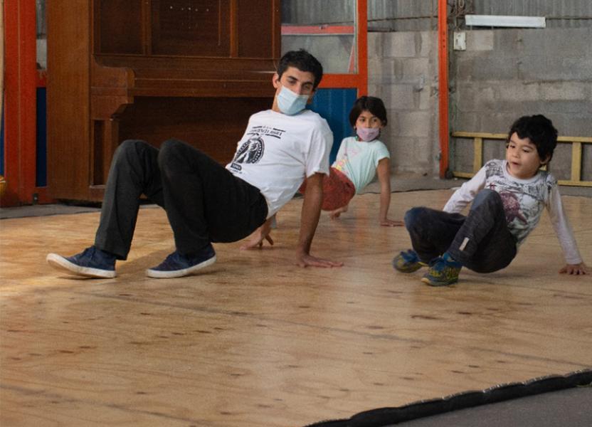 Profesor junto a alumnos y alumnas practicando poses de Capoeira sobre el piso.