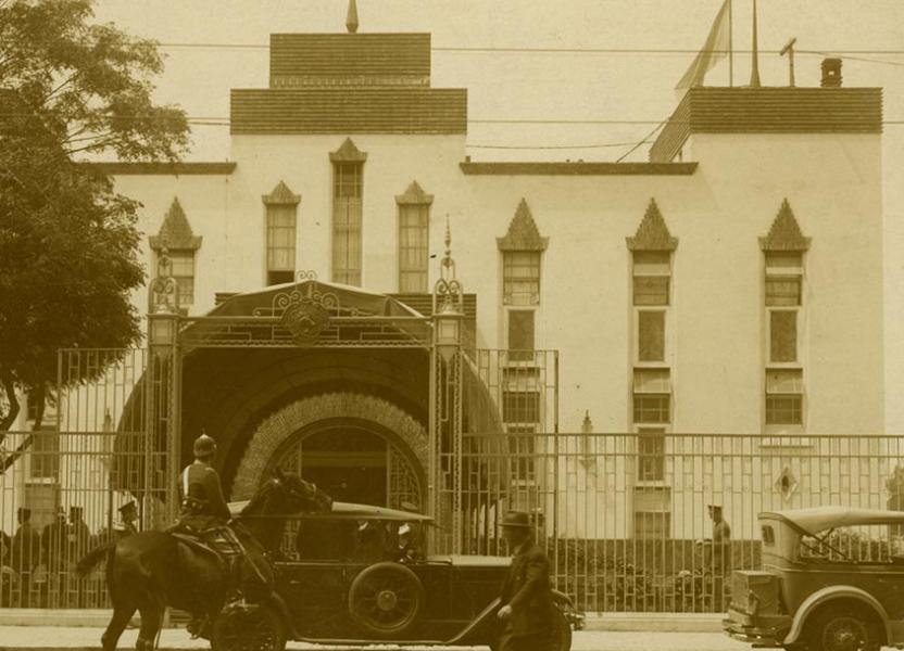 Entrada principal al Hipódromo del Parque de la Independencia, a mediados de la década del 20. En primer plano se observan dos coches estacionados , un hombre cruza de a pie, y de a caballo un policía.