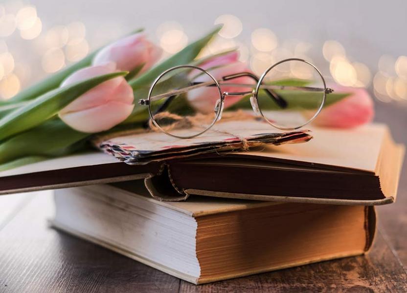 Varios libros apilados con unos lentes de lectura sobre ellos enfocados hacía la cámara.