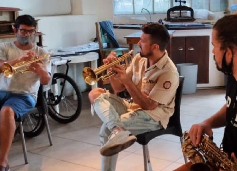 Dos personas sentadas en semi circulo mirando a una tercera, quien les muestra la posición de los dedos sobre una trompeta para que repliquen.