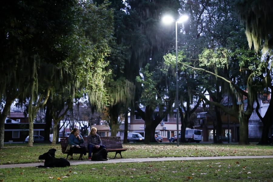 Chicas en el parque sentadas en un banco por la noche