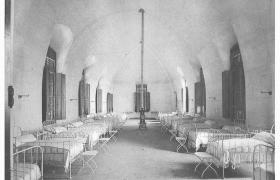 Hospital Rosario, sala de internación. Se observa en ambos laterales de la habitación una línea de camas sin personas y en el centro una estufa. Álbum de Gestión Municipal de Luis Lamas, 1902.